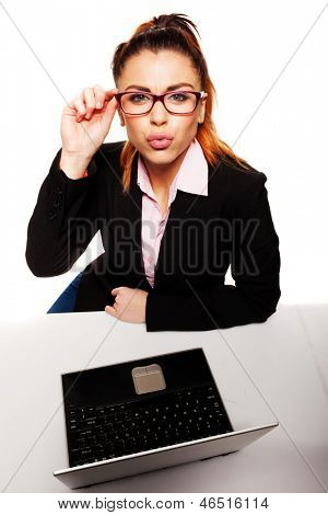 Flirty and provocative business woman holding glasses and whit a laptop over the desk