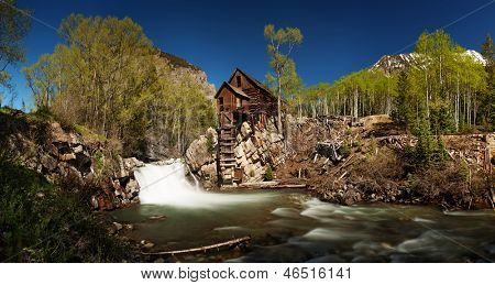 Scenic panorama of Crystal Mill in Colorado showing the historical power house perched on a rocky outcrop above the Crystal River against a backdrop of the Rocky Mountains