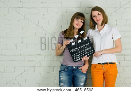 Two Young Smiling with a Clapboard