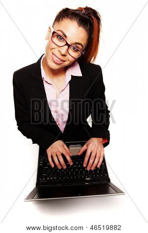 High angle view of a woman working on a laptop wearing glasses and looking up at the camera with a smile