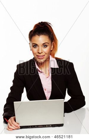 Smiling attractive business woman in the office sitting behind her open laptop computer looking at the camera on white