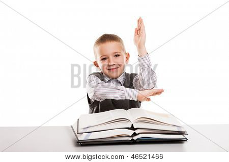 Little smiling child boy with education books at desk gesturing hand up for answering school homework lesson