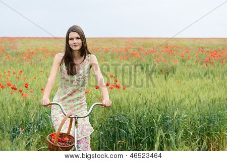 Young beautiful woman with bicycle and basket with cherry on a poppy field, summer outdoor.