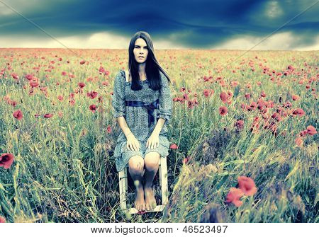 Mysterious portrait of young beautiful woman sitting on stool in a poppy field and looking at camera, summer nature outdoor. Toned.