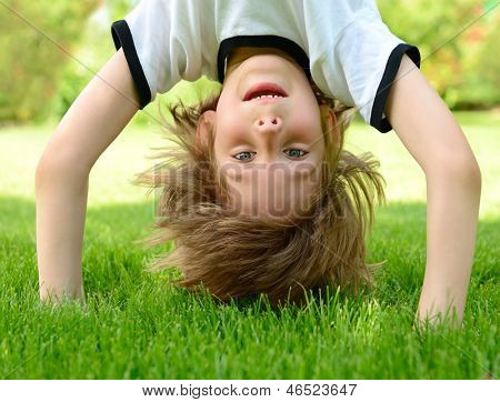 Happy little boy standing upside down on green grass in spring park.