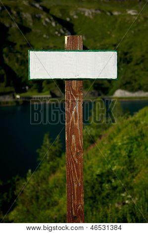 Blank, empty signpost in a mountain landscape
