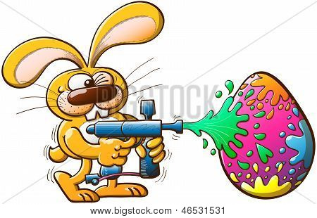 Easter bunny decorating his egg by shooting colors with a gun