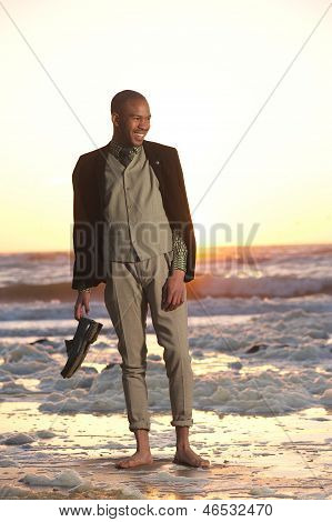 Young Man Standing On The Beach With Shoes In Hand