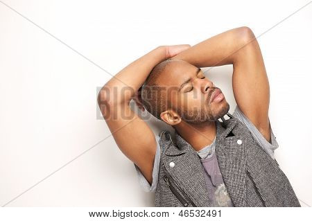 Male Fashion Model Posing With Hands On Head Against White Background