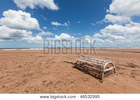 Broken lobster trap rests on a vast Prince Edward Island beach.