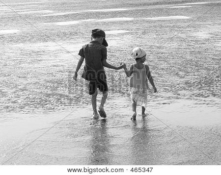 Beach Shot With Kids Walking Hand In Hand