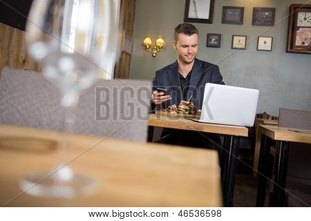 Young business man with laptop and mobilephone having meal in restaurant