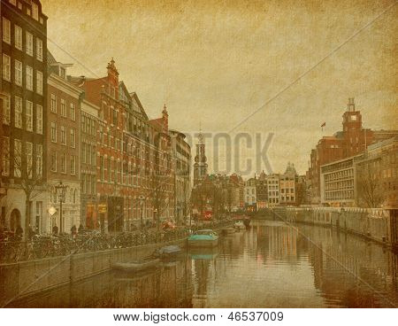 The Singel is one of the numerous canals in Amsterdam,  Netherlands . In the background Munttoren .Photo in retro style. Paper texture.