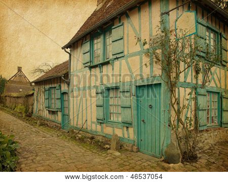 Gerberoy.  Old house in medieval village. Gerberoy is a commune in the Oise department in northern France.  Photo in retro style. Paper texture.