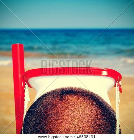 picture from the back of a man wearing a diving mask and a snorkel on the beach, with a retro effect