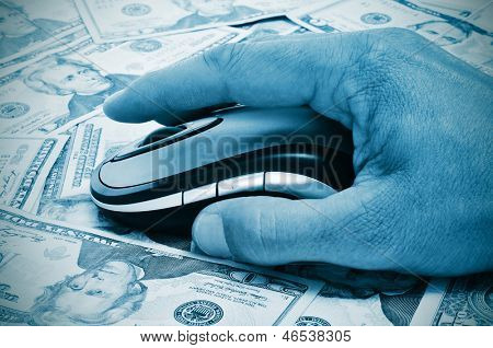 a hand man using a computer mouse on a background full of dollar banknotes, depicting the e-commerce concept or the internet fraud concept