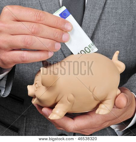 closeup of a man wearing a suit introducing a euro bill in a piggy bank