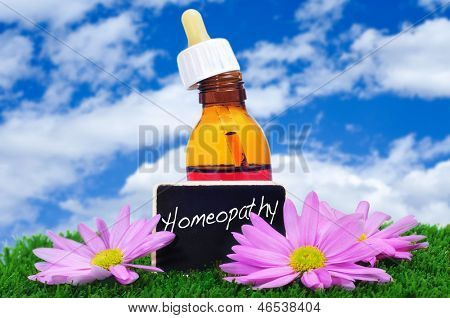 a dropper bottle and some purple flowers on the grass with a blackboard label with the word homeopathy written on it