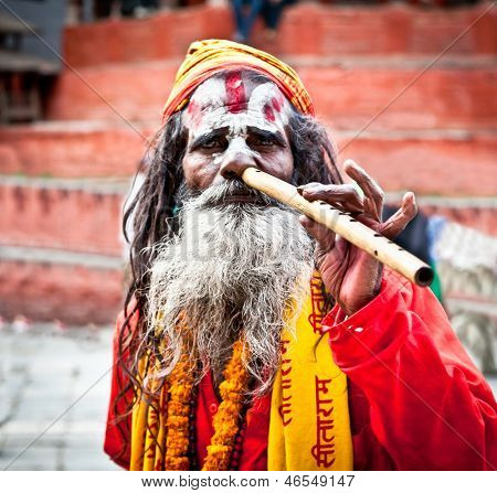 KATHMANDU,NEPAL-MAY 18: Sadhu play flute at Pashupatinath Temple in Kathmandu, Nepal on May 18, 2013. The two primary sectarian divisions in sadhu community are Shaiva sadhus and Vaishnava sadhus.