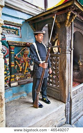 KATHMANDU - MAY 18: Nepalese guard standing in front of the Hanuman Dhoka, Royal Palace gate at May 18, 2013 in Kathmandu, Nepal. This palace has been an UNESCO World Heritage site since 1979
