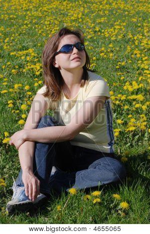Woman Sitting In Field Of Dandelions