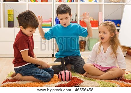 Children Playing With A Piggybank