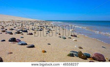 Sunny Beach with Colorful Stones