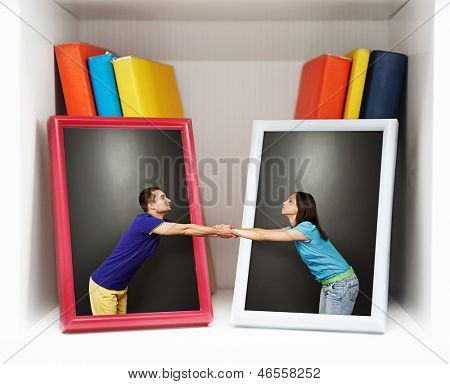 romantic photo of young couple. boy and girl reaching out to each other from pictures