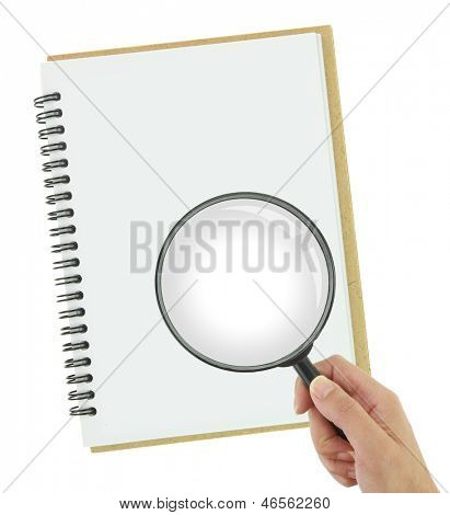 Hand holding magnifying glass over blank notebook
