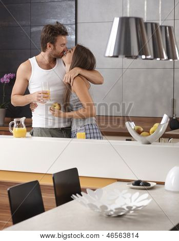 Young loving couple kissing in the kitchen in the morning, having breakfast.