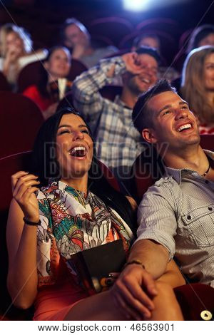 Happy couple watching comedy in movie theater, laughing.
