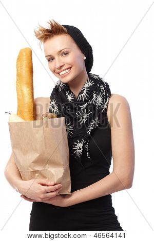 Happy young woman holding full shopping bag.
