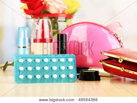 Hormonal pills in women's bedside table on room background