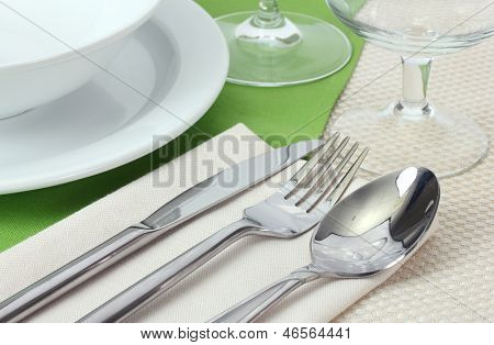 Table setting with fork, knife, spoon, plates, and napkin
