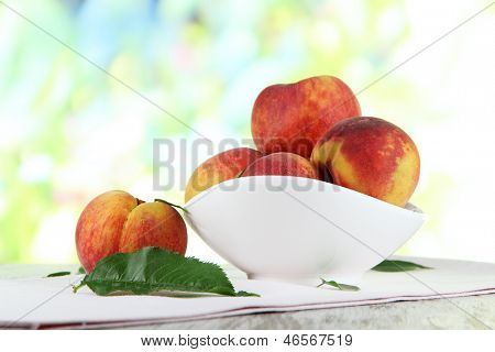 Peaches in plate on napkin on wooden table on nature background
