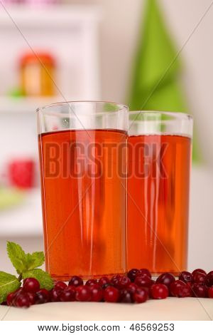 Glasses of cranberry juice and ripe red cranberries on table
