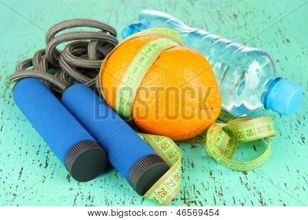 Orange with measuring tape,skipping rope and bottle of water, on color wooden background