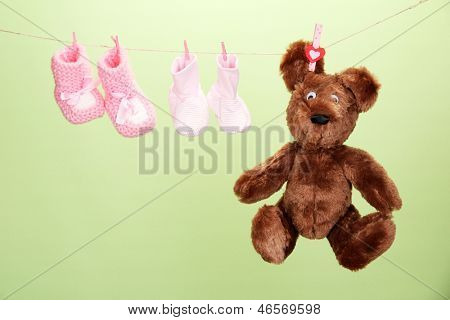 Baby booties hanging on clothesline, on color background