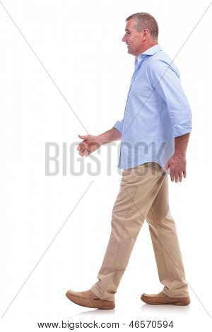 side view of a casual senior man walking and looking forward. isolated on white background