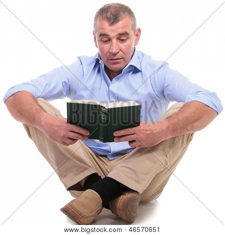 casual senior man sitting on the floor with his legs crossed and reading a book with interest. isolated on white background