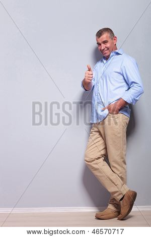 full length picture of a casual senior man standing with a hand in his pocket and showing thumbs up while smiling for the camera. on gray background