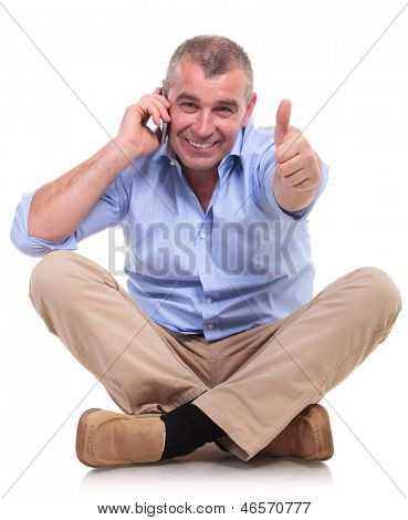 casual senior man sitting on the floor with his legs crossed and talking on the phone while showing thumbs up gesture and a smile for the camera. isolated on white background