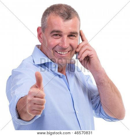 casual senior man showing thumb up sign while talking on the telephone and smiling for the camera. isolated on white background