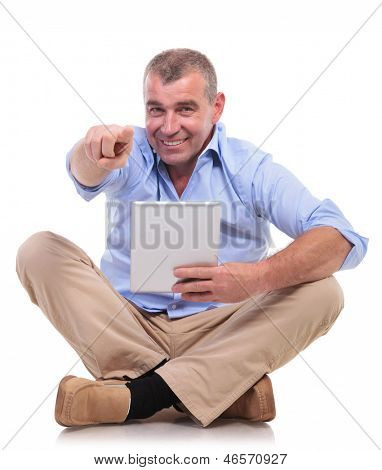 casual senior man sitting on the floor with his legs crossed and holding his tablet while pointing and looking at the camera. isolated on white background