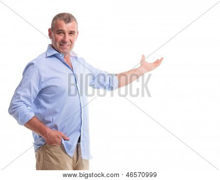 casual senior man presenting something while holding a hand in his pocket and looking at the camera. isolated on white background