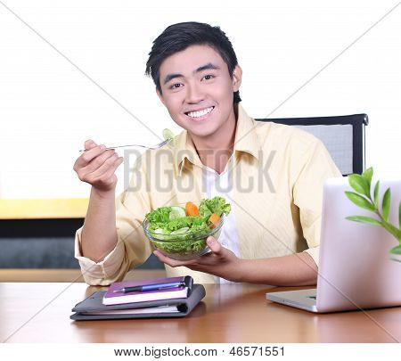 Asian young business man eating snack in the office