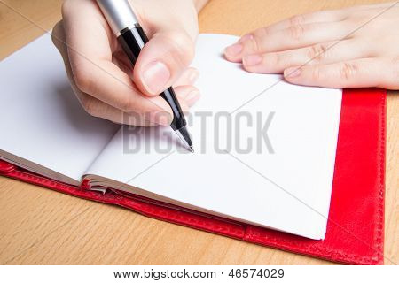 Escritura en el cuaderno rojo