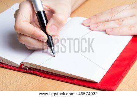 Mano de mujer joven tomando notas