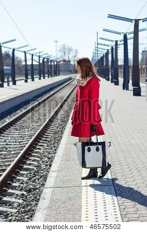 Young Woman In Red At A Train Station