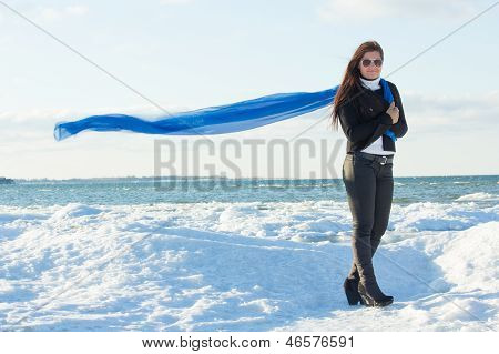 Portrait Of Young Woman With Blue Scarf On Winter Beach